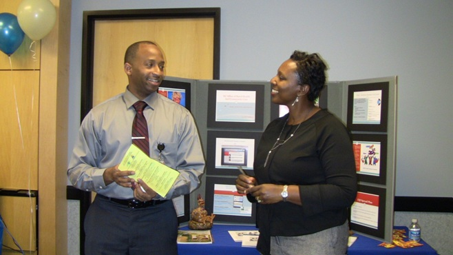 Colleagues exchanging QI ideas and information during a poster session at the NC Division of Public Health.